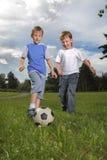 男孩作用足球 免版税图库摄影