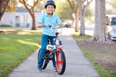 男孩佩带的安全帽骑马自行车 免版税库存图片