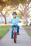 男孩佩带的安全帽骑马自行车 图库摄影