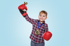 男孩佩带的拳击手套和庆祝成功与金黄战利品 免版税库存照片