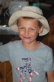 年轻男孩佩带的边缘帽子微笑 免版税库存图片