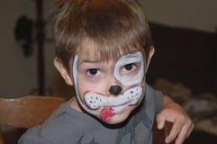 年轻男孩佩带的面孔油漆小狗设计 库存图片
