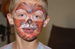 年轻男孩佩带的面孔油漆老虎设计 库存照片