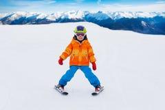 男孩佩带的滑雪帽和盔甲滑雪在倾斜 免版税图库摄影