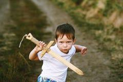 男孩使用与一把木剑 免版税库存图片