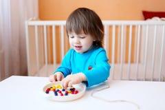 2年男孩使用与各种各样的颜色小珠  库存照片