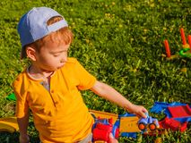 男孩使用与在绿色草坪的一辆玩具汽车 免版税库存照片