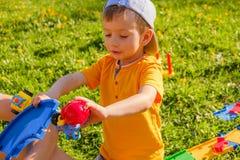 男孩使用与在绿色草坪的一辆玩具汽车 库存照片