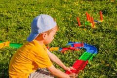 男孩使用与在绿色草坪的一辆玩具汽车 库存图片