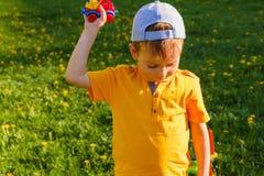 男孩使用与在绿色草坪的一辆玩具汽车 图库摄影