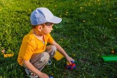 男孩使用与在绿色草坪的一辆玩具汽车 免版税库存图片