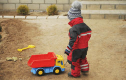 男孩使用与在街道上的一辆大玩具卡车 免版税库存照片