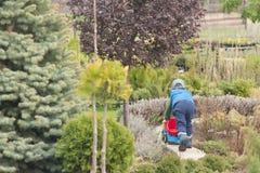 男孩使用与在街道上的一辆大玩具汽车在乡间别墅里,在水坑的雨以后,胶靴 免版税库存照片
