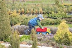 男孩使用与在街道上的一辆大玩具汽车在乡间别墅里,在水坑的雨以后,胶靴 图库摄影