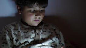 男孩使用与在黑暗的片剂前面去睡眠起重机射击 影视素材