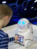 男孩使用与在黑暗的背景的一个机器人与亲笔文书 免版税库存照片