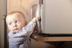 男孩使用与微波炉定时器的儿童孩子  库存照片
