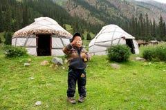 男孩使用与肥皂泡靠近谷的农夫房子在中亚山  免版税库存照片
