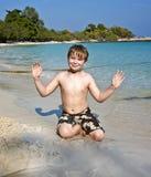 男孩使用在与沙子和大厦形象的海滩 免版税库存照片