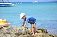 男孩使用在海岸的,石头 免版税库存照片