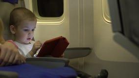 男孩使用在片剂app的两岁,和在航空器位子坐 库存图片