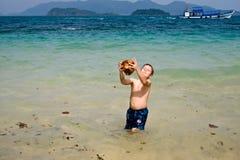 男孩使用用在海滩的一个椰子 免版税库存照片