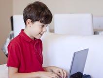 男孩使用年轻人的计算机膝上型计算&# 免版税图库摄影
