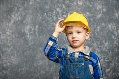 男孩保持建筑盔甲和微笑 图库摄影