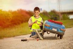 男孩修理他减速火箭的玩具汽车 免版税库存照片
