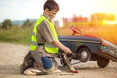 男孩修理他减速火箭的玩具汽车 图库摄影