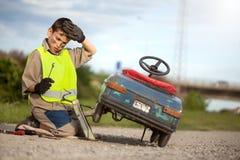 男孩修理他减速火箭的玩具汽车 免版税库存图片