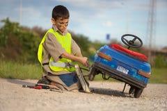 男孩修理他减速火箭的玩具汽车 库存图片