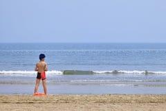 年轻男孩俯视海滩的,烟台,中国海 免版税库存照片
