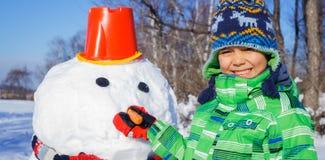 男孩做一个雪人 免版税库存照片