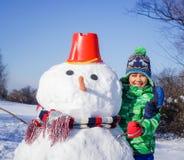男孩做一个雪人 免版税库存图片