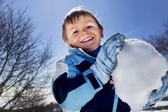 男孩做在山的一个大雪球,冬天乐趣 库存照片