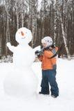 男孩做雪人 免版税库存照片