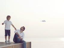 男孩做飞行他的有他的父亲`的s纸飞机帮助 库存图片
