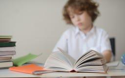 男孩做他的坐在学校书桌的家庭作业 免版税库存图片