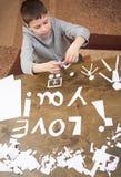 男孩做origami -汽车和家庭,孩子,父母,我爱你文本,在木背景的顶视图 库存图片