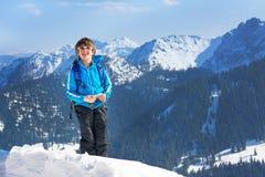 男孩儿童冬天山顶面上升 库存照片