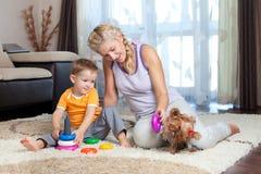 男孩儿童狗室内母亲使用 免版税库存照片