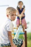男孩儿童看起来庭院的女孩演奏夏天摇摆, 男孩在焦点和女孩被弄脏后边 库存图片