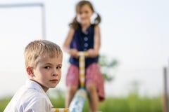 男孩儿童看起来庭院的女孩演奏夏天摇摆, 男孩在焦点和女孩被弄脏后边 图库摄影