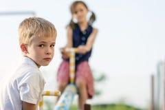 男孩儿童看起来庭院的女孩演奏夏天摇摆, 男孩在焦点和女孩被弄脏后边 免版税库存照片