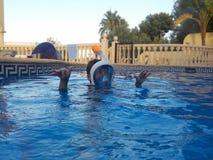 男孩充当与Easybreath面具的一个游泳池 免版税图库摄影