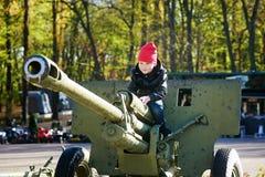 男孩充当军用设备博物馆  库存图片