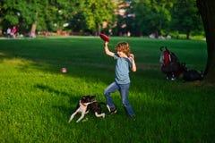 男孩充当有狗的公园 免版税库存照片