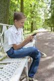 男孩充当电话在公园 库存图片