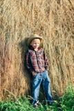 男孩全长画象懒惰农夫,倾斜的干草姿势的  免版税库存图片